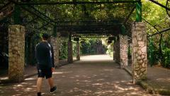 Man Walks Under Huge Canopy In Park - stock footage