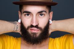 Man with beard and piercings - stock photo