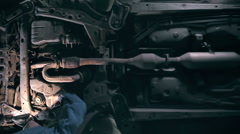 Mechanic examines the underside of a car Stock Footage
