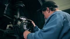 Mechanic inspecting car brake discs - stock footage