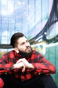 Cool guy with beard and piercings sitting outdoors - stock photo