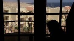 Woman closes the curtains and doors to the balcony overlooking the sea - stock footage