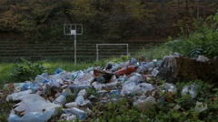 Pile of garbage close up, tilt up, sun shining through the forest treetops. Stock Footage