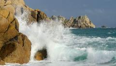 Waves break on sunlit rocks, Porthcurno, Cornwall, UK - stock footage