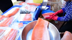 Fish seller in market place at work Stock Footage