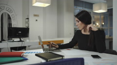A woman working at the computer, taking notes on a sheet, crumples and throws Stock Footage
