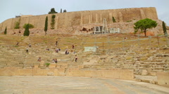 Many tourists viewing ancient Theater of Dionysus remains, amphitheater seats Stock Footage
