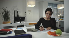 Woman working and eating slices of carrots and apples. Stock Footage