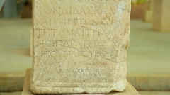 Text in Greek language on ancient stone table, antique exhibit at history museum Stock Footage