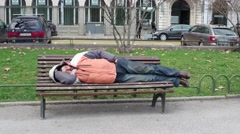 The homeless sleeps on a bench in a public park in the city center daytime Stock Footage