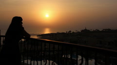 Woman watching the sunset on the balcony overlooking the sea Stock Footage