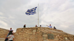 Greek flag on top of ancient Acropolis, tourists taking photos, debt crisis Stock Footage