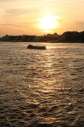 pleasure boat floats on the river at sunset - stock photo