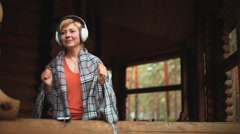 Girl in headphones listens to music on the wooden veranda Stock Footage