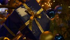 Moving through christmas tree towards a gift parcel - stock footage