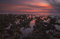 Beautiful Vibrant Sunset Over the Sea with Rocks in Foreground - stock photo