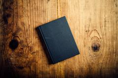 Black notebook on wooden office desk Stock Photos