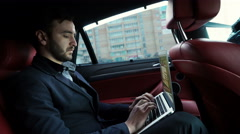 Businessman working in back of car and using a tablet Stock Footage