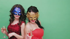 Two young girls in sexual Venetian masks. Studio green background - stock footage