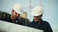 Engineer and client looking on project on the construction site - stock footage