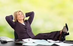 Relaxing mature business woman. Green background - stock photo