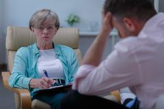 Personal counselor helping stressed man Stock Photos