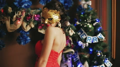 A young beautiful sexy girl in the mask near Christmas tree Stock Footage