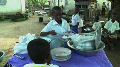 ADEISO SCHOOL LUNCH: BOY STUDENT SELLS FOOD AND COLLECTS MONEY Stock Footage