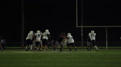 A football player moves past his opponents and runs toward the end zone Stock Footage