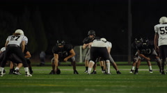 A football player fights his way down the field toward the end zone at night Stock Footage