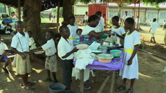 ADEISO SCHOOL LUNCH: WOMAN SERVES FOOD Stock Footage
