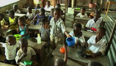 ADEISO SCHOOL LUNCH: WIDE PAN OF YOUNG STUDENTS EATING IN A CLASSROOM - stock footage