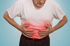Stomach ache, man placing hands on the abdomen Kuvituskuvat