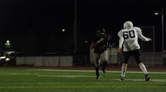 A football player runs hard to catch the football during a game Stock Footage