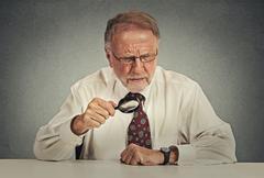 Senior grumpy businessman looking through magnifying glass - stock photo