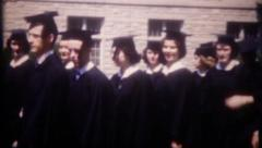 2895 - parade of graduates on college campus - vintage film home movie Stock Footage