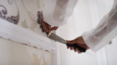 Female hands removing wallpaper in a house - stock footage