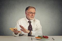 Senior man eating fresh salad avoiding fatty pizza - stock photo