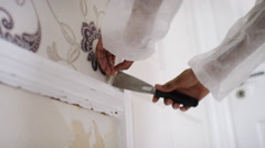 Female hands removing wallpaper in a house, in slow motion - stock footage