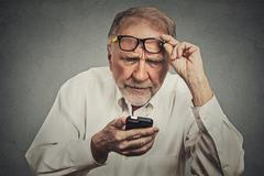 elderly man with glasses having trouble seeing cell phone - stock photo