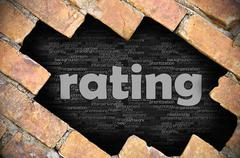 Hole in the brick wall with word rating - stock photo