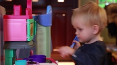 Cute baby girl playing with toy kitchen furniture - stock footage