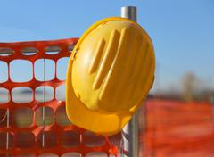 hard hat on the road construction site during road works and a safety net - stock photo