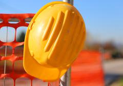 Hard hat on the road construction site during road works and a safety net Stock Photos