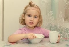Little girl eats porridge from sitting at the table. - stock photo