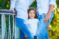 Very cute little blonde girl holding the foot mom and dad. hug Stock Photos