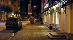 A passer-by a man walks down an empty city street at night Stock Footage