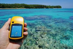 GPS satellite navigator in hand over tropical sea Stock Photos