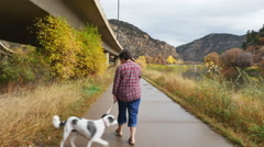 Unidentifiable woman walks black & white dog under elevated section of I-70-1 Stock Footage