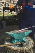 Blacksmith forges iron on anvil - stock photo